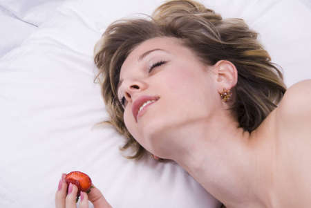 Young woman lying down with sex toys on a bed Stock Photo - 7556713