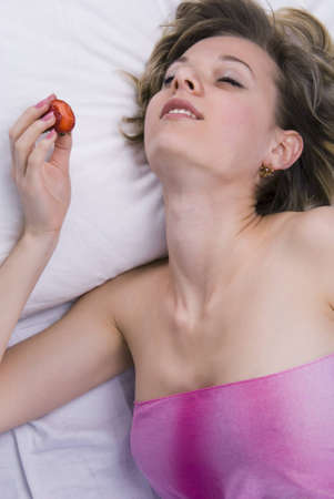 Young woman lying down with sex toys on a bed photo