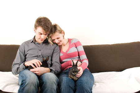 Young couple with rabbits on the couch Stock Photo