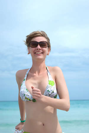 Young happy woman running from the ocean Stock Photo