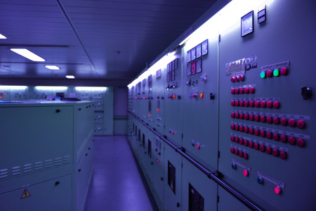 engine room: Engines and control panels in a ship engine room in bluish gloom light. Stock Photo