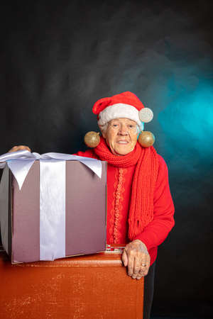 A cheerful, old woman, in a New Years cap, with a large present in her hands. Studio photo. Dark background. Congratulations on Christmas. High quality photo 写真素材