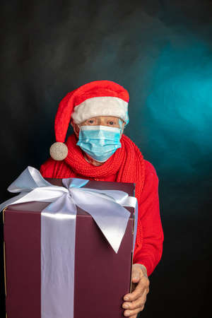 An old woman, in a medical mask, in a New Years cap, with a large gift in her hands. Studio photo. Dark background. Congratulations on Christmas. High quality photo