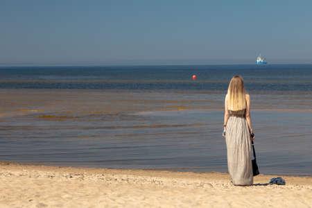 Ust-Narva, Ida-Viru County, Estonia,, Ida-Viru County, Estonia, June 23, 2020. On the beach, sunny day, A girl in a long gray dress looks at the sea. High quality photo
