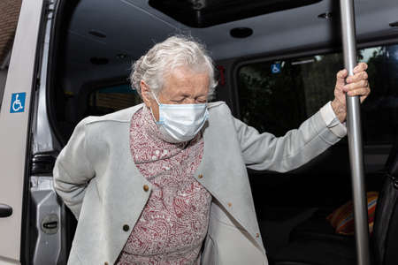An old woman in a medical mask with a wheelchair, getting a disabled person into the car. High quality photo Stock Photo