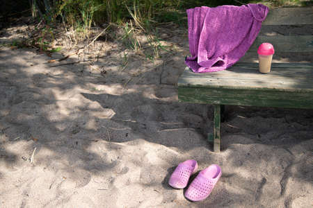On the beach, bench, pink slippers, towel, shaker. High quality photo