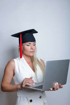 Beautiful blonde graduation cap holds a laptop in her hand, studio light background. Concept, education, learning remotely, online. High quality photo