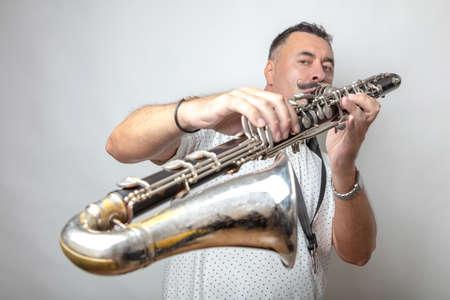 A man, dark, short hair, plays the bass clarinet. Studio, light background. High quality photo
