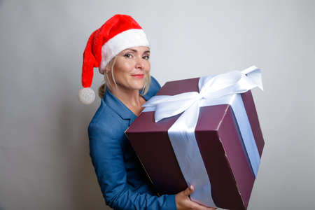 Blonde with long hair in a Santa hat, Big gift with a white bow in her hands. Studio, light background, Happy New Year greetings. High quality photo