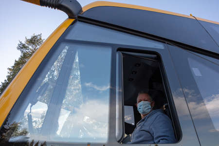 Bus driver wearing a medical mask, looking out of the bus window Safe driving during a pandemic, protection against coronavirus. High quality photo