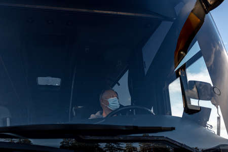 Bus driver wearing a medical mask, from the side of the frontal window Safe driving during a pandemic, protection against coronavirus. High quality photo