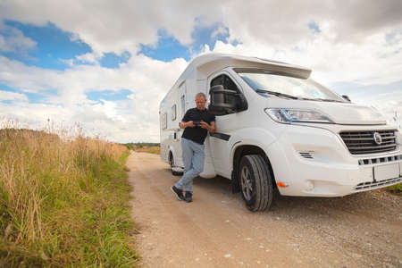 A man looks at the phone at a motorhome on a country road in the middle of fields. Summer sunny day. High quality photo