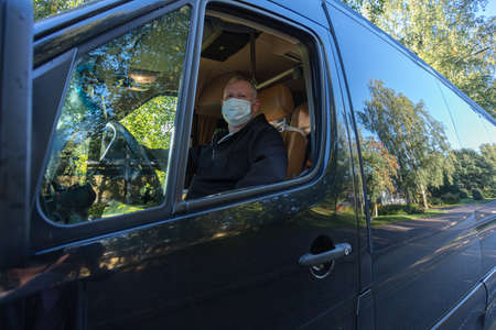 Driver in a medical mask leads a black bus Safe driving during a pandemic, protection against coronavirus. High quality photo