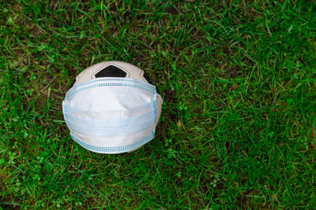 Against the background of grass, A medical mask is on the ball, there is a place for text. Concept protecting children from coronavirus. High quality photo
