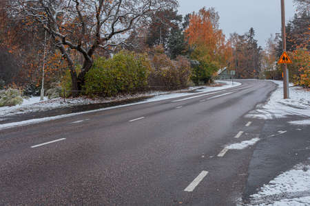 Scenic autumn view with first snow on the road, trees and forest in snow and hoarfrost against a cloudy sky background. High quality photo