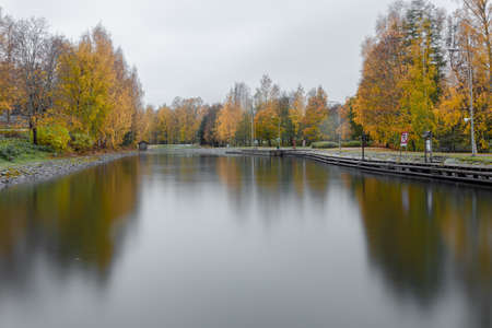 View of the canal, in autumn, yellow birches on the bank and reflection in the water. Its a nasty day . High quality photo