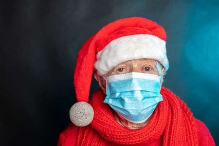 An elderly woman in a Christmas cap and a medical mask. Concept, congratulate your parents and loved ones Happy New Year. High quality photo Stockfoto