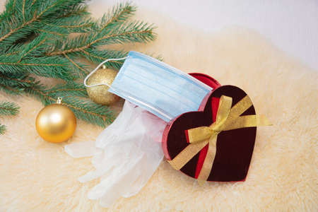 The gift box contains a medical mask with latex gloves, a spruce branch and Christmas decorations