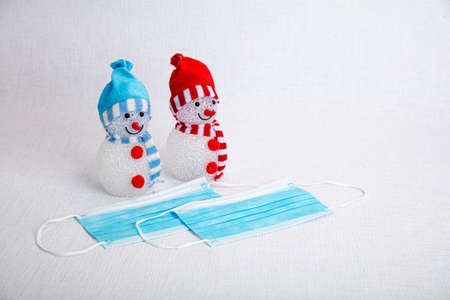 Two snowmen with face mask on white