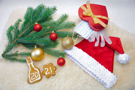 The gift box contains a medical mask and latex gloves, a spruce branch and Christmas decorations and a Christmas hat. Concept, congratulations Happy New Year 2021. On a white background. High quality photo Stock Photo