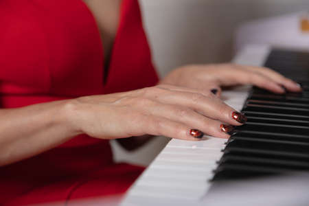 Close-up, female hands on the keys of the piano. On the background of a red dress. High quality photo Standard-Bild