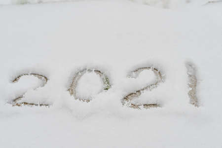 Text written in the snow, 2021. Cadaveric plan. Happy New Year greetings concept. High quality photo
