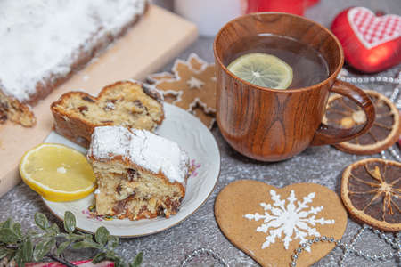 Christmas roll, tea with lemon in a wooden mug. New Years tinsel. Celebratory still life. High quality photo Archivio Fotografico