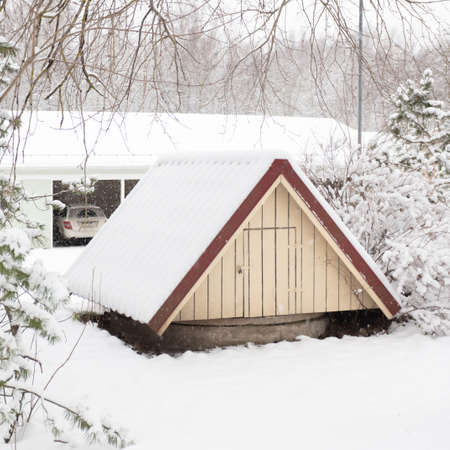 winter, rural landscape,. The well is covered with snow, against the background of covered garages with cars. High quality photo
