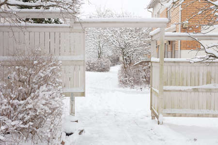 White wooden fence and courtyard entrance. Winter snow day. High quality photo