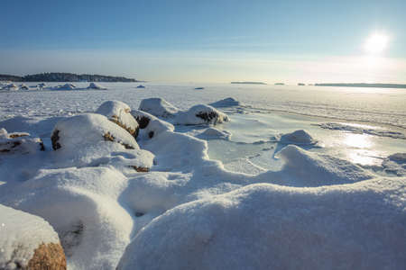Winter landscape, frozen sea, coastal strip under the snow, sunny day. Finland, Espoo,. Concept. snowy winter. High quality photo