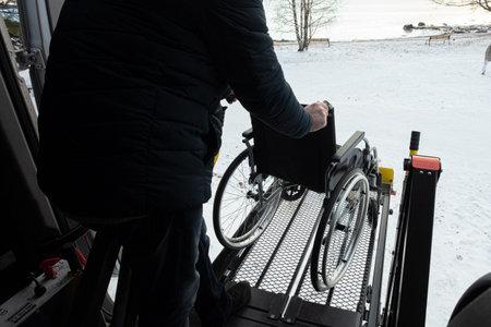 A man unloads a wheelchair from a car. High quality photo