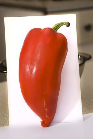 red pepper in the kitchen on a white sheet of paper with a nice big hot green tail