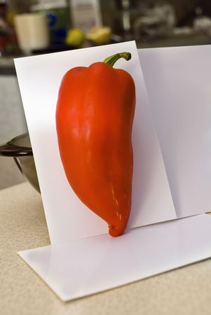 red pepper in the kitchen on a white sheet of paper with a nice big hot green tail photo