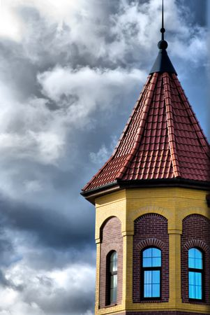 a large tower on the background of sky blue, cloudy color with old windows and the roof of acute