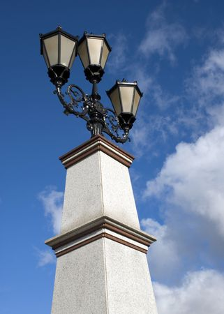 street lamp on a pedestal against the background of blue sky a bright colorful summer