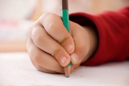 child writes, girl wrote a childrens hand with a pencil sheet of white paper with a picture sleeve on red soft background on a table studying a happy childhood education Stock Photo