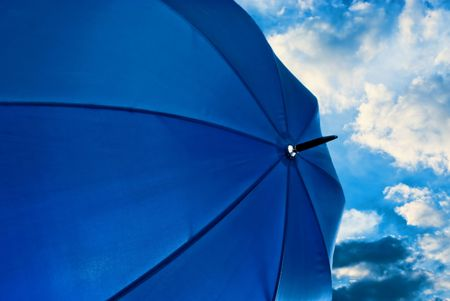 umbrella from the rain blue huge against the blue sky with clouds nicely