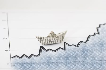 business Concept with a chart showing growth and a paper boat on a sea texture photo
