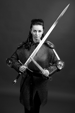 monochrome portrait of a medieval female knight in armour over grey background