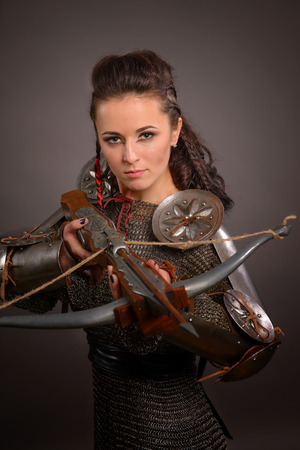 Portrait of a medieval female knight in armor with a crossbow on a gray background
