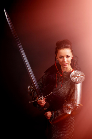 portrait of a medieval female knight in armor on a gray background with a side red light