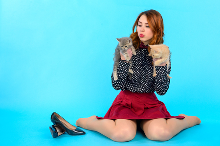 young girl with long hair and in fashionable clothes sits on a blue background and holds two cats, next to her are her black shoes Фото со стока