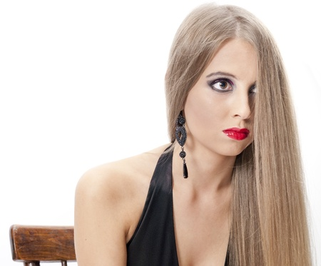 Beautiful woman with evening make-up sitting on the chair over white. Fashion photo photo