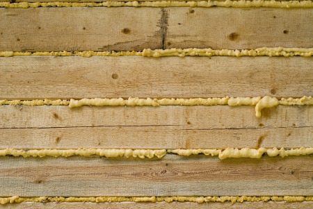 Close-up of Polyurethane foam filling gap in wooden construction, background photo