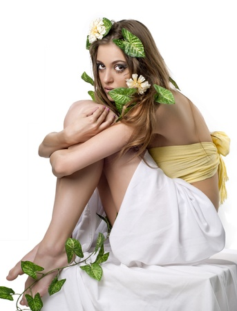 Beautiful young lady with flower and leaf  in her hair posing in studio photo