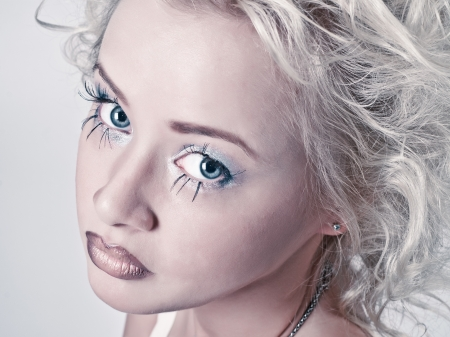 Attractive blond beauty portrait with original make up and hair dress