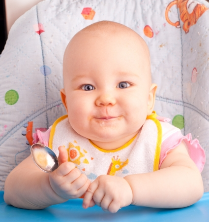 the infancy: Little baby feeding with a spoon at the kitchen