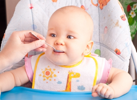 Little baby feeding with a spoon at the kitchen photo