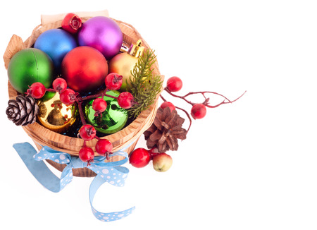 Christmas background with wood bucket, cones, color balls and berries for beautiful Holiday design photo