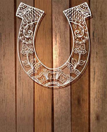 buena suerte: herradura con el ornamento floral, símbolo de la suerte sobre fondo de madera